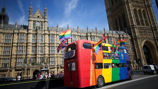 Carro com ativistas gay passando em frente ao Parlamento (Foto: The Australian/AFP)